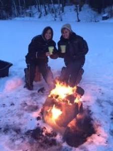Sandy and Lesa relaxing by a fire on the ice.